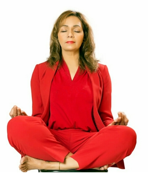 A woman doing  Sukhasana by seating in a relaxed cross legged pose with eyes close and breathing slowly.