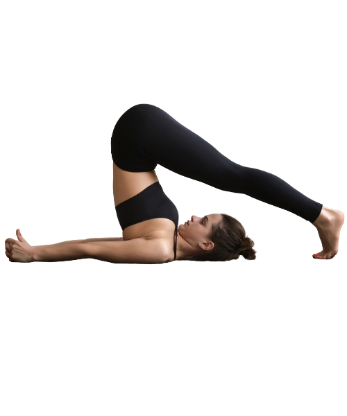 A woman doing halasana by lying on floor bending backward touching the ground with legs (one of the  yoga poses to boost metabolism)