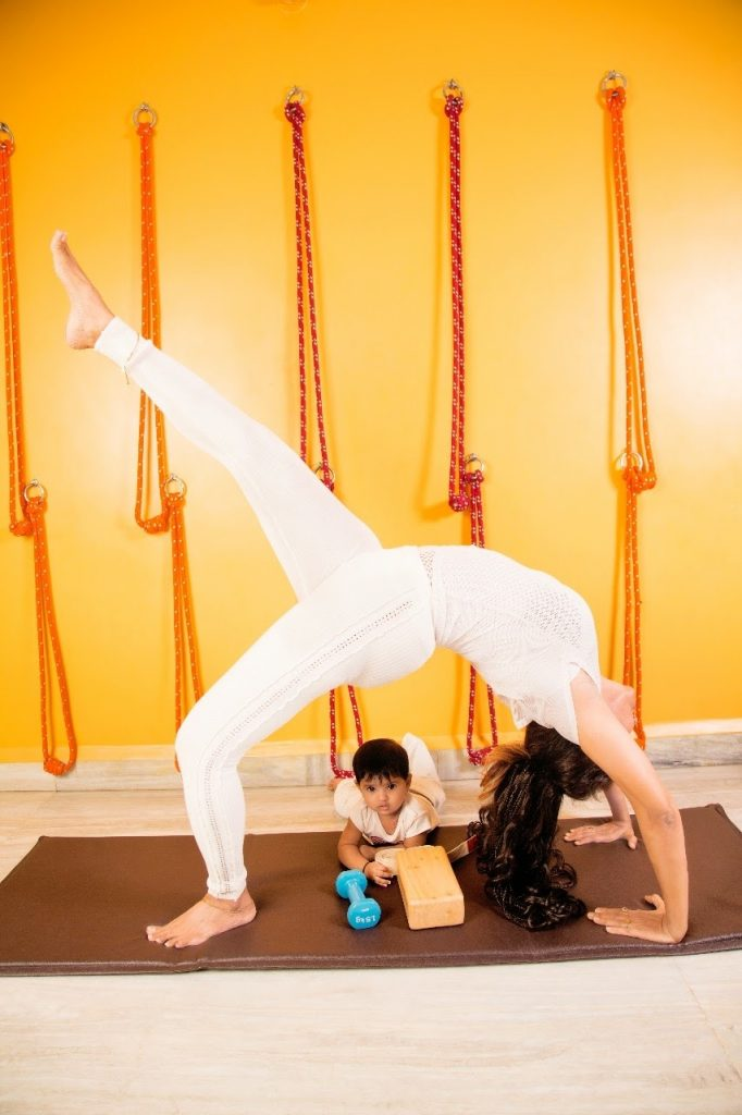 Kids Yoga - A lady performing yoga and kid is playing at Shwetyoga Classes & Courses in Thane