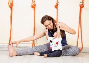 Image shows a yoga instructor with a small kid