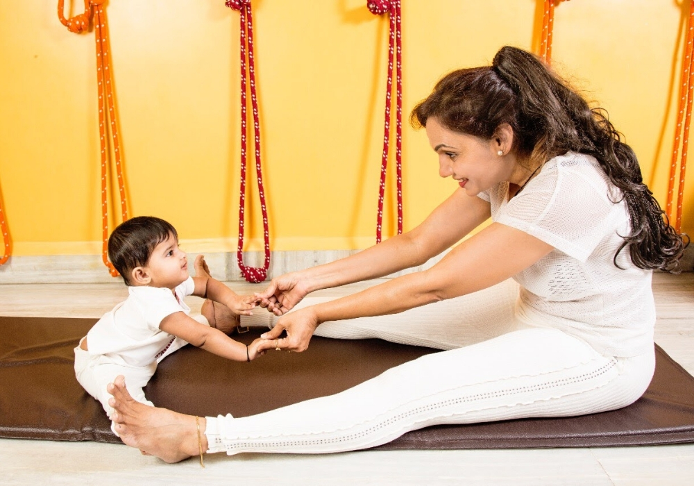 Yoga instructor lovingly teaching kid the yoga asana