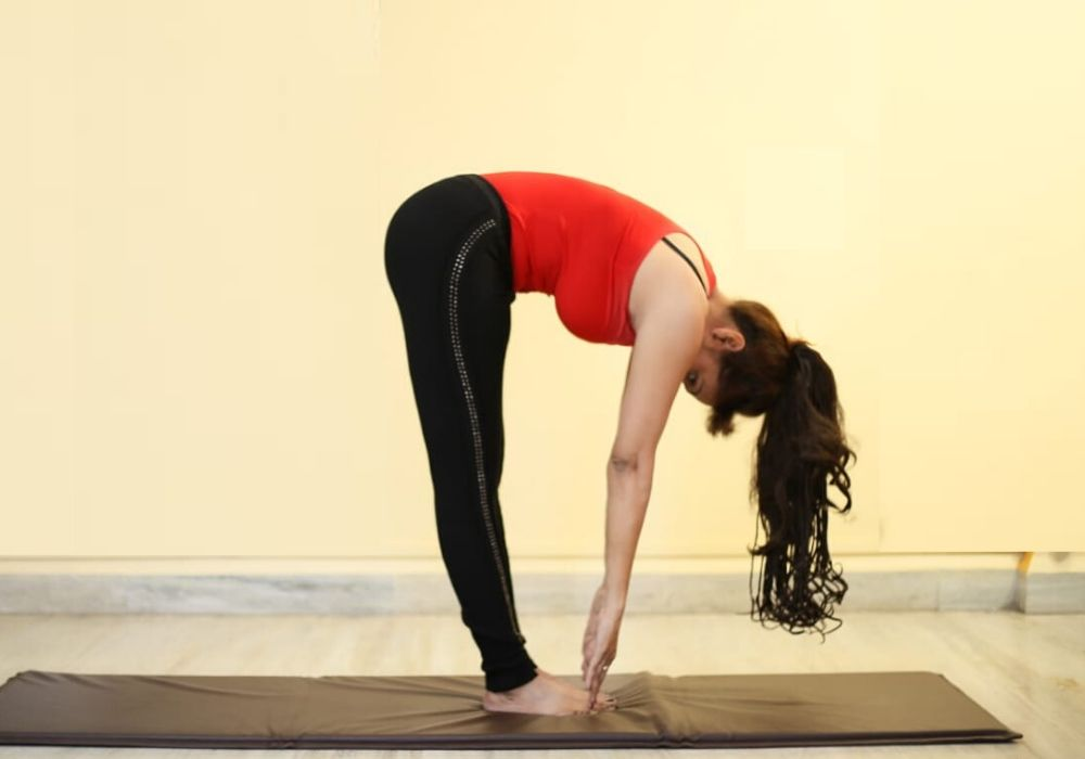 A woman doing uttanasana at yoga classes in thane as, yoga do wonders to your skin.