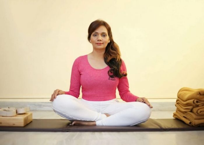 Dr. Shweta Varpe seating on yoga mat at Shwet yoga claases in thane to perform yoga to cure asthma without drug